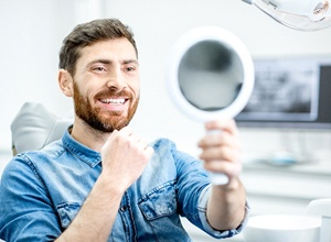 Man smiling in mirror, happy with investment in ceramic crown